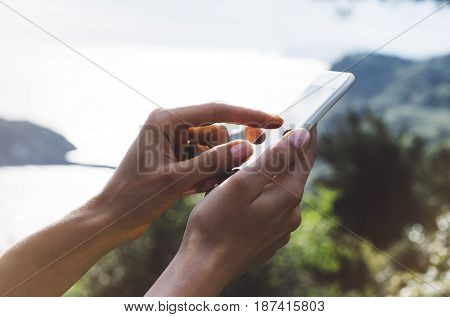 Hipster girl texting message on smartphone mobile close up view tourist hands using gadget phone on device travel on background green mountains landscape; finger touch screen cellphone mockup nature