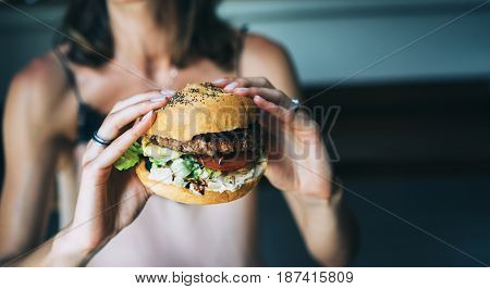 Young girl holding in female hands fast food burger american unhealthy calories meal on background mockup with copy space for text message or design hungry human with grilled hamburger front view