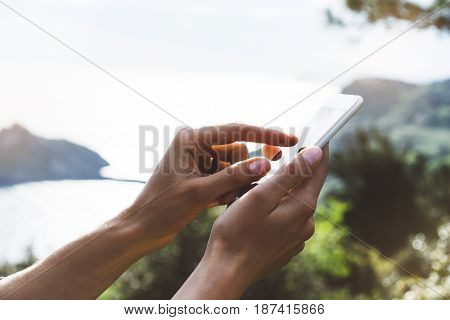 Hipster girl texting message on smartphone mobile close up view tourist hands using gadget phone on device travel on background green mountains and blue sky landscape; finger touch screen cellphone mockup nature