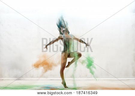 Female sexy gymnast in gray bodysuit shot in a jump on white background in a cloud of orange and green dust all over body