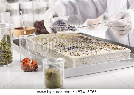 Laboratory Worker Dressed In White Gown And Gloves Holding Glass Container With Seeds Working Experi
