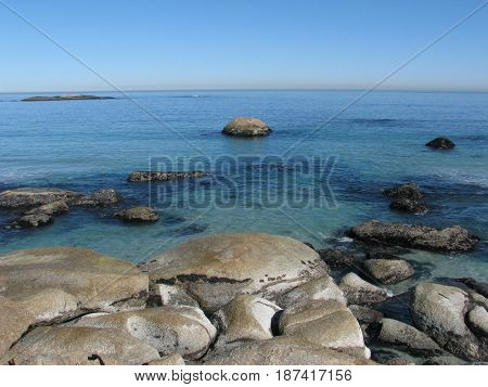 FROM CAMPS BAY, CAPE TOWN, SOUTH AFRICA,HUGE BOULDERS IN FORE GROUND, WITH A BLUE  BACK GROUND HORIZON