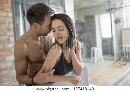 Athletic topless guy with closed eyes hugs his girlfriend in a black sleeveless. She leans on the headboard with closed eyes. Indoors. Closeup. Horizontal.