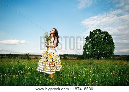 A Beautiful Young Free Girl In A Light Dress With Lemons And A Bouquet Of Wildflowers, In The Middle