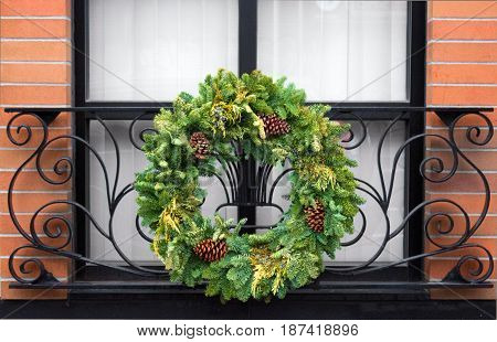 festive winter holiday wreath on window grate