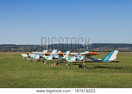 Small and light airplanes stand on a lawn of field airfield waiting for a departure in summer sunny day.
