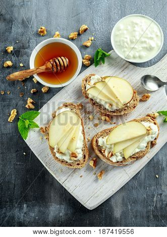 Appetizer bruschetta with pear, honey, walnut and cottage cheese on white board