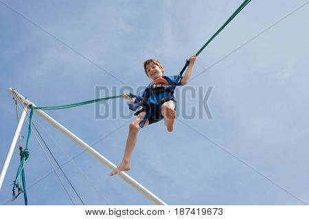 Young boy enjoying jumping with trampoline jumping rope
