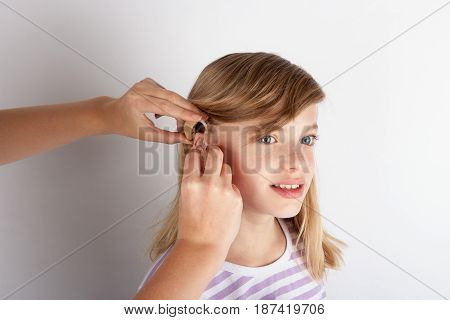 Close up of a Doctor's hands fitting a hearing aid for a young girl patient .