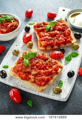 Fresh homemade crispy Italian appetizer Bruschetta topped with tomato, eggplant, Zucchini, Yellow pepper, garlic and basil on white wooden board. healthy food.