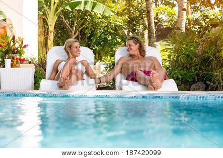 Young couple sunbathing and lying on sunbeds, summer vacations