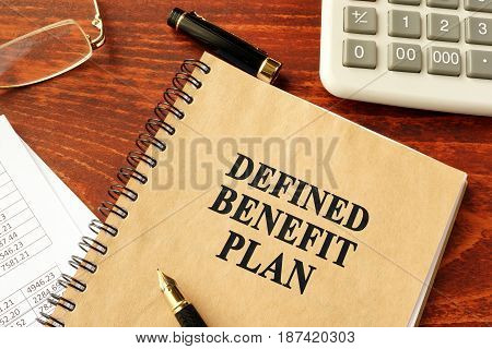 Book with title Defined Benefit Plan and calculator.