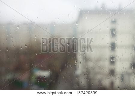 A view of the city through a wet window glass. Autumn rainy weather