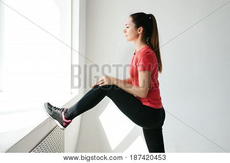 Pretty young girl looks out the window and does warming exercises and stretching before training. Single sports.
