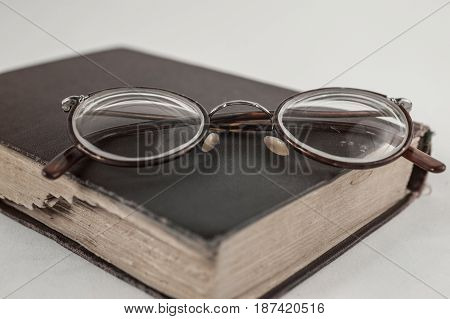 Old Grandmother's Glasses And A Dilapidated Book