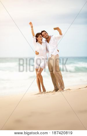 Young couple making selfie on beach