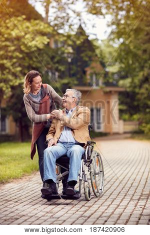 Happy caregiver daughter with senior man in wheelchair