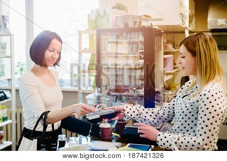 Woman Paying With Credit Card In A Cafe