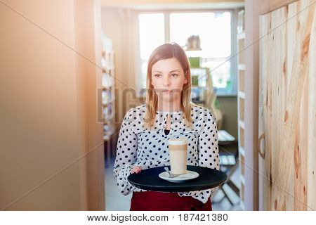 Waitress In The Cafe Carries A Tray With Cafe Latte
