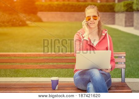 Urban casual woman sitting on a bench in the park. She is talking on mobile phone and holding laptop. Coffee cup to go is next to her.
