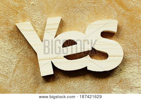 Wood word yes on a wood background