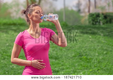 Fitness runner woman drinking water in the park. Athlete girl taking a break during run to hydrate during hot summer day. Healthy active lifestyle.