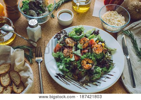 Concept making tasty and healthy food at home. Ingredients and cutlery around fresh salad with shrimps. Serving option