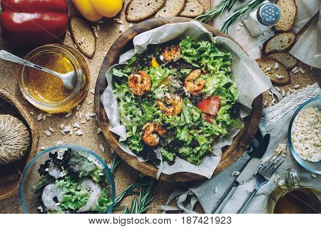 The concept making tasty and healthy food at home. Ingredients and cutlery around fresh salad with shrimps. Serving option. Flat lay style