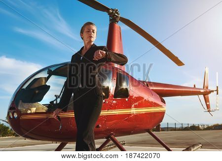 Business woman near the helicopter. Business success and luxury concept