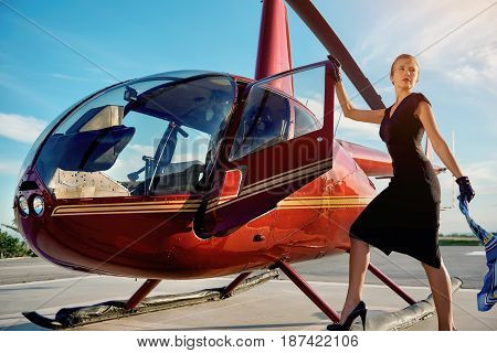 Elegant business woman flying away by the helicopter. Business success and luxury concept