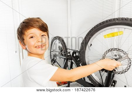 Close-up portrait of happy six years old boy repairing his bicycle wheel with spanner