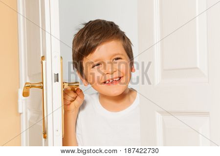 Close-up portrait of happy Caucasian kid boy  looking through the doorway