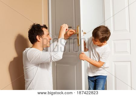 Portrait of young father teaching his kid son to repair the door handle at home