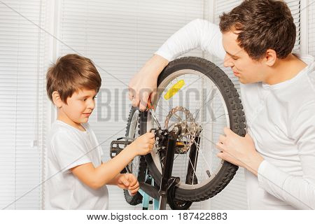 Portrait of young father repairing bicycle using pliers with his kid son