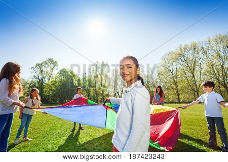 Portrait of smiling African girl playing colorful parachute with her friends outdoor at sunny day