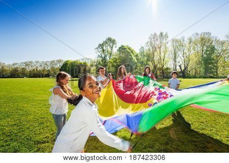 Portrait of happy African boy waving colorful parachute full of little balls with her friends at sunny day
