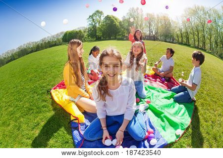 Fish eye picture of laughing girl sitting on rainbow parachute and holding colorful balls in her hands, playing with friends in summer park