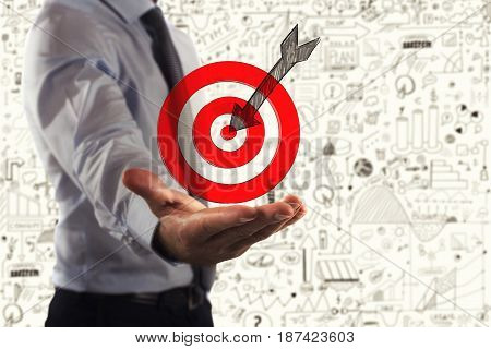 Businessman holds in his hand a Target hits in the middle by arrow