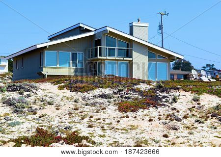 Coastal sand dunes with a vacation beach house beyond