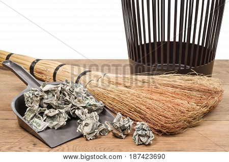 Crumpled dollars in a garbage shovel next to a broom and a bucket on a wooden surface on a white background