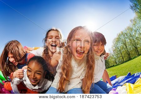 Big group of cute kids hugging and laughing during outdoors party in the park