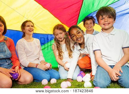 Big group of six happy kids, 10-12 years old boys and girls, sitting under canopy made of rainbow parachute