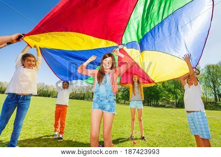 Joyful kids playing with rainbow parachute, standing under it's big canopy in the park