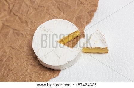 Fresh slice Camembert cheese natural, on Kraft paper brown background. With clipping path