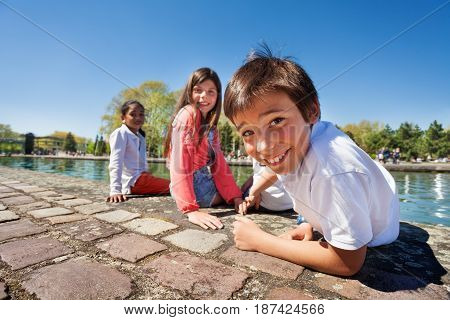 Close-up portrait of cute ten years old boy sitting on the embankment with his friends in summer