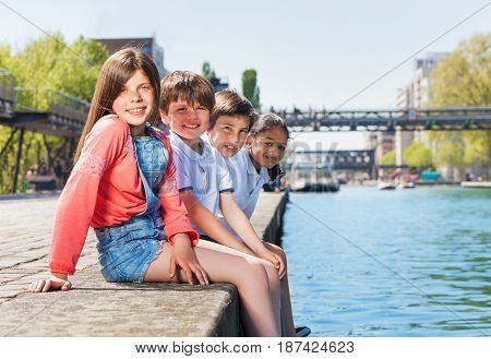 Portrait of four multiethnic kids, 10-12 years old boys and girls, sitting in a line on embankment in summer