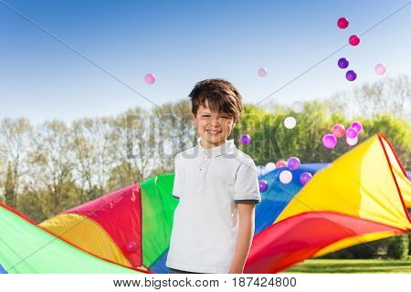 Portrait of smiling boy playing rainbow parachute and colorful balls in the spring park