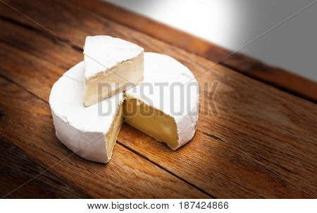 French Camembert cheese on rustic wooden table background