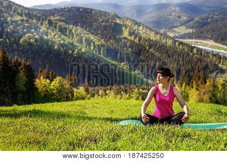 The young girl sitting on a mountaintop. The concept of a healthy lifestyle travel and yoga.