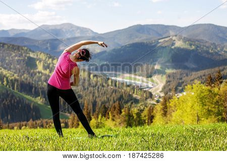 The young girl practices yoga on the mountain. The concept of a healthy lifestyle travel and yoga.